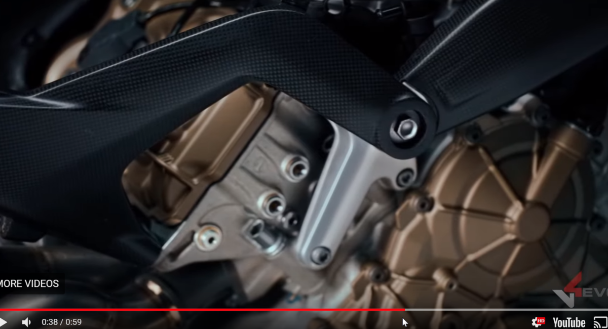 The carbon subframe bolts directly to the top mount, overlapping the carbon frame spur.