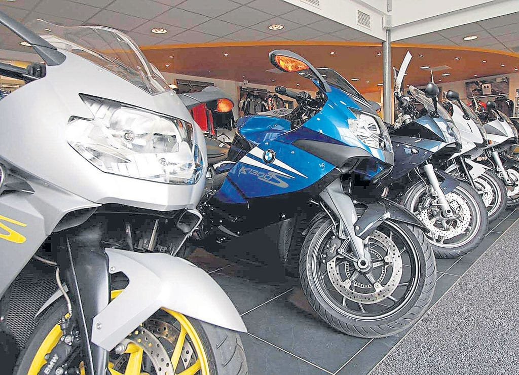 A row of motorcycles in a bike shop.