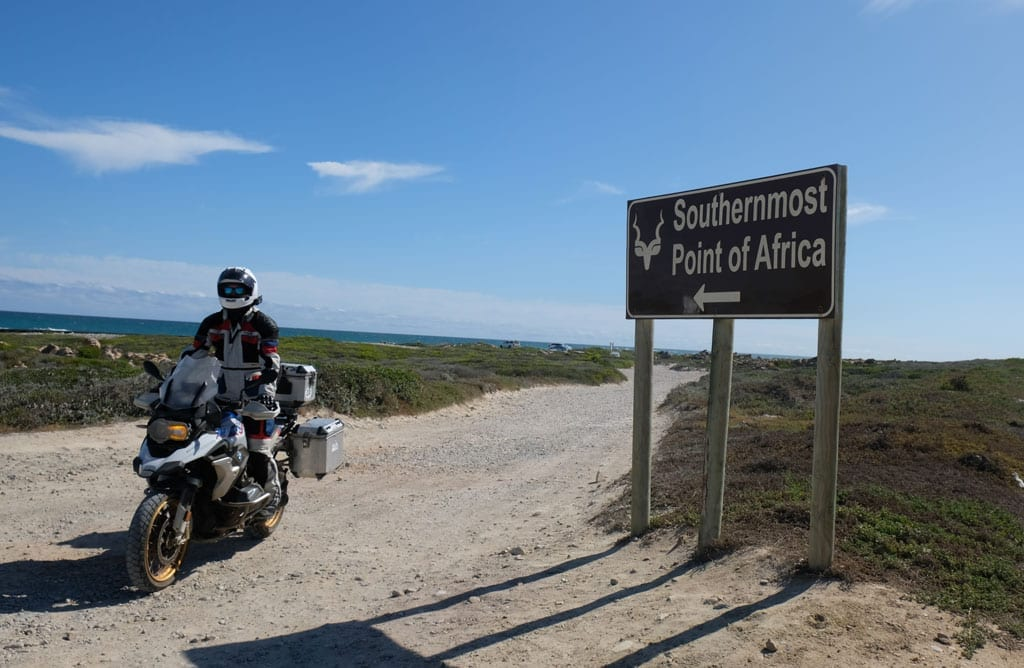 One of the bikers sits on their bike next to a sign saying 'Southernmost point of Africa'.