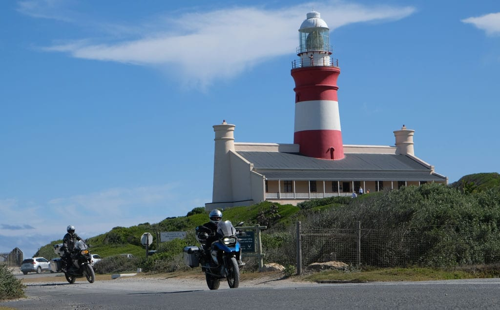 Two of the bikers ride past a lighthouse.