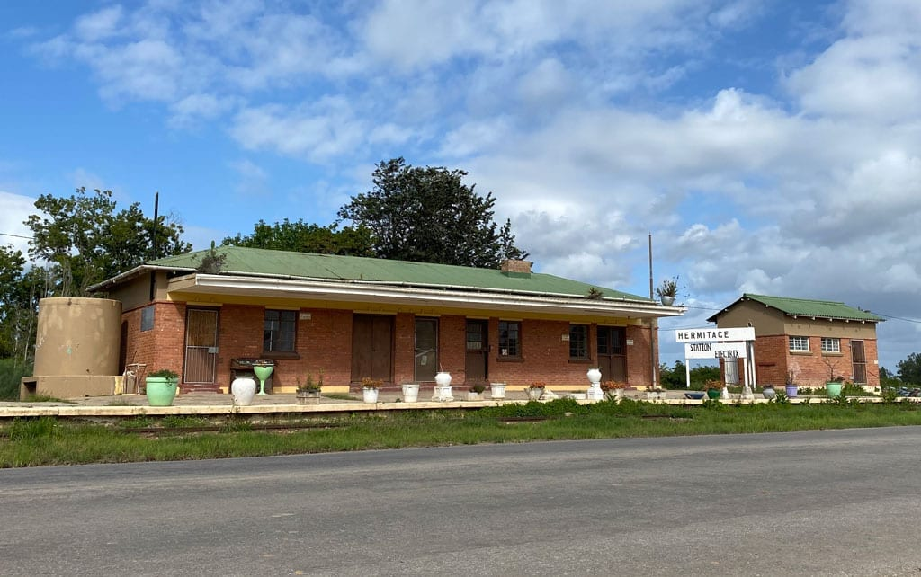 A pair of small, seemingly closed buildings on the side of the road.