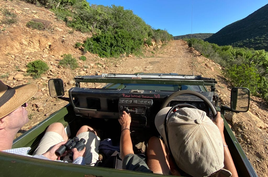 The group drive a small jeep along a small dirt road.