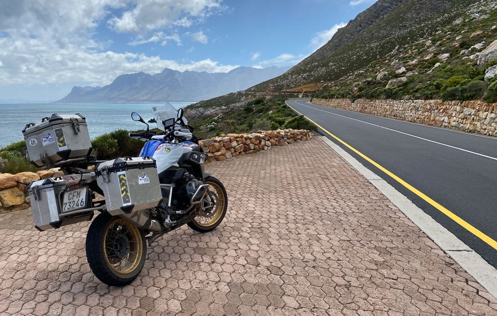 One of the bikes parked on the side of the road with a scenic view in the background.