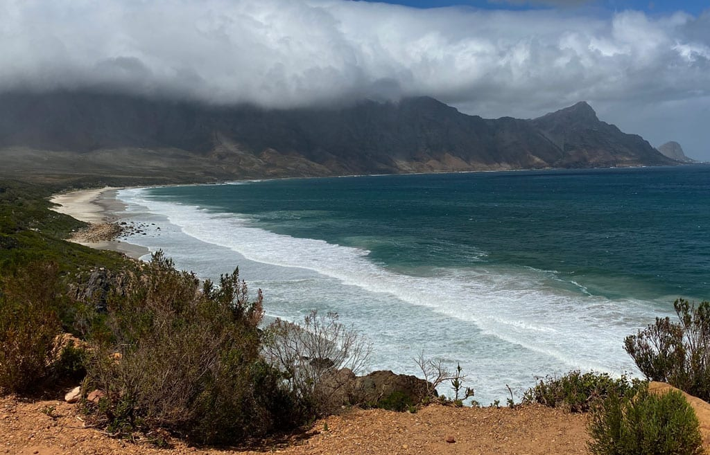 A view of the coast with the sea and misty mountains in the background.